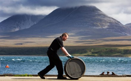 Whisky cask being rolled in Islay, Scotland