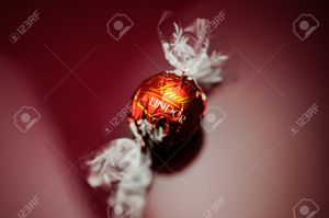KILCHBERG, SWITZERLAND - MARCH 20, 2014: Lindt Lindor chocolate truffle on a red luxury silk background as seen on March 20, 2014. Lind is one one of the lastgest luxury chocolate and confectionery company worldwide